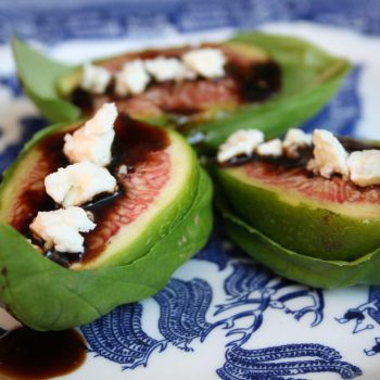 Figs with balsamic drizzle and feta on a basil leaf