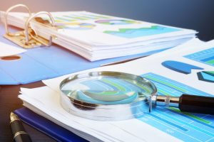 Financial audit report and magnifying glass on a desk.