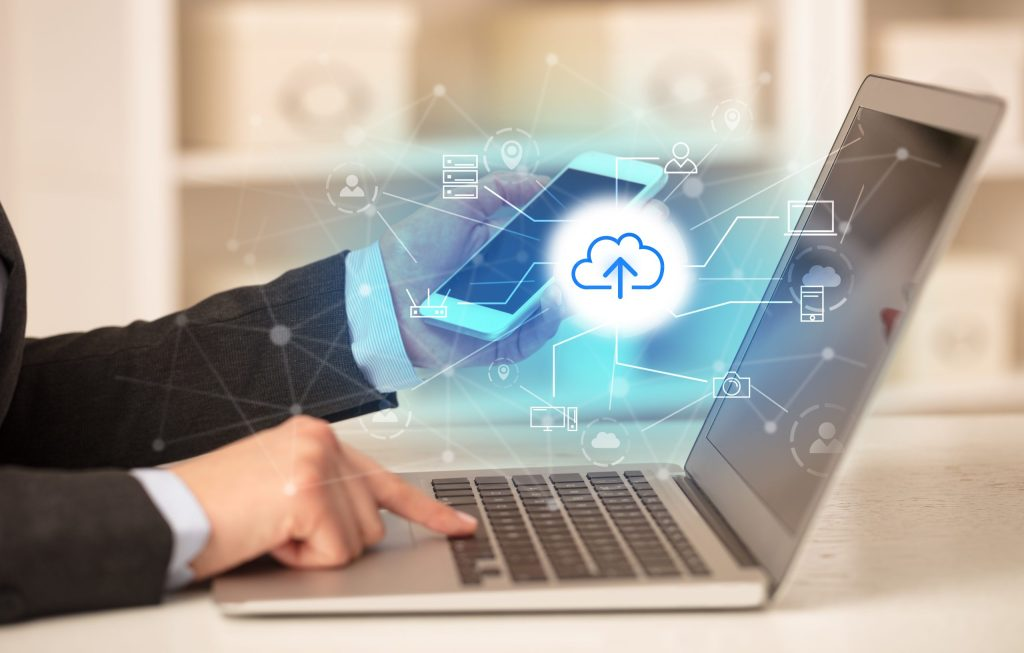 Business woman working on her laptop with online storage and cloud technology concept