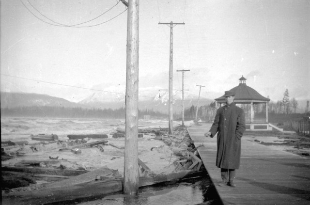 Man standing on wooden sidewalk at shore of Kitsilano Beach during a storm, 191?. Image:  Major Matthews
