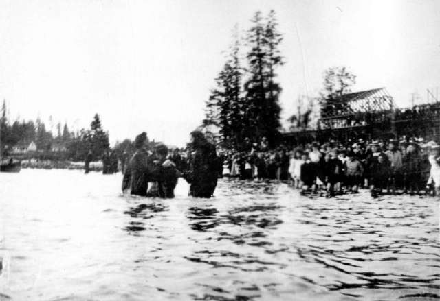Woman being baptized by the Reverends Christmas and Fair in English Bay Omage: Vancouver Archives