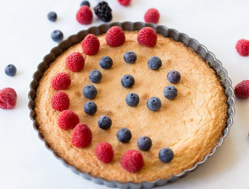 This Almond Cake recipe uses 5 basic ingredients to create a chewy, almond-infused cake, perfect for topping with berries and powdered sugar.