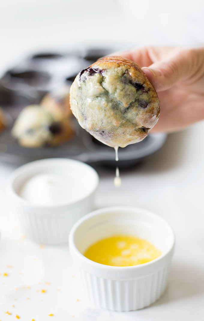 Blueberry-Orange Muffins made with freshly-grated orange zest and juicy blueberries. Dipped in orange-infused butter and sprinkled with sugar!