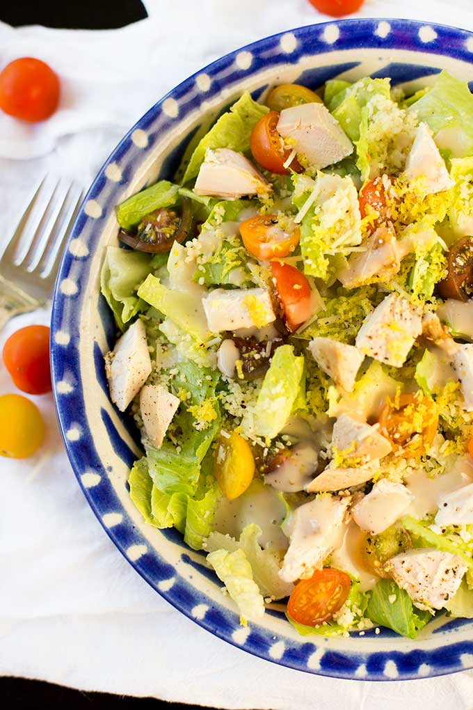 Roasted chicken, couscous, tomatoes, grated cheese, lemon zest, all tossed in a light Caesar dressing...this Chicken Couscous Caesar Salad is a keeper!