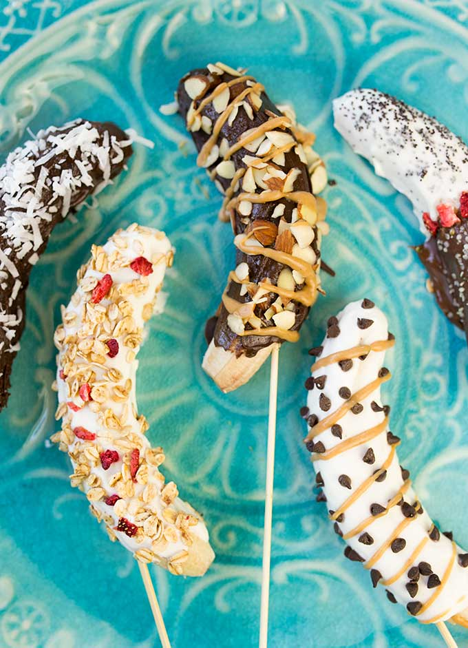 Frozen Banana Pops are a fun, sweet treat to beat the heat! Dipped in chocolate and/or Greek yogurt and topped with nuts, coconut, chia, peanut butter, etc.
