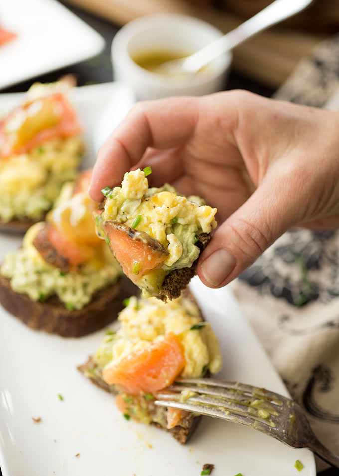 Smoked Salmon and Egg Avocado Toast: simple scrambled eggs, avocado cream cheese and salmon on a piece of pumpernickel, drizzled with dill vinaigrette.