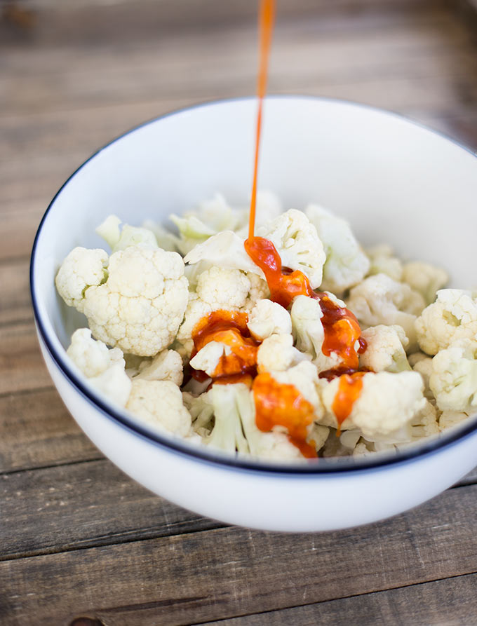 Roasted Buffalo Cauliflower: Sriracha, honey and a little olive oil blended together create the perfect spicy sauce for crispy roasted cauliflower!