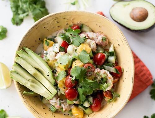 Coconut Lime Ceviche: shrimp, mango, tomato, cucumber and jalapeño bathed in a coconut lime sauce! All the flavors of the Caribbean in one delicious bowl.