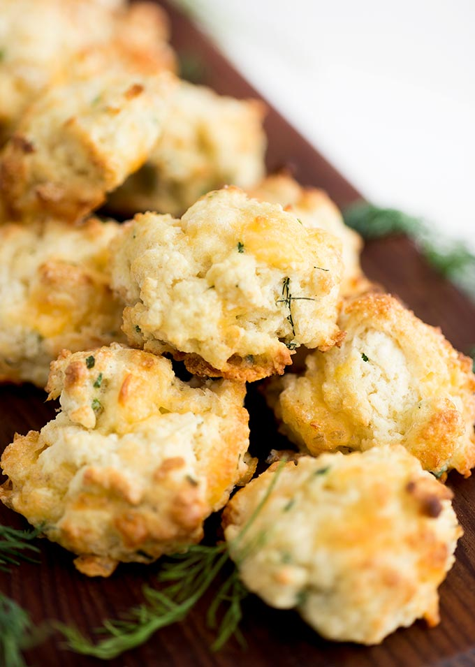 Cheddar Herb Scones - flaky, buttery and full of flavor, these scones won't disappoint! Each bite is full of fresh herbs and cheddar cheese, the perfect combo for a delicious scone.
