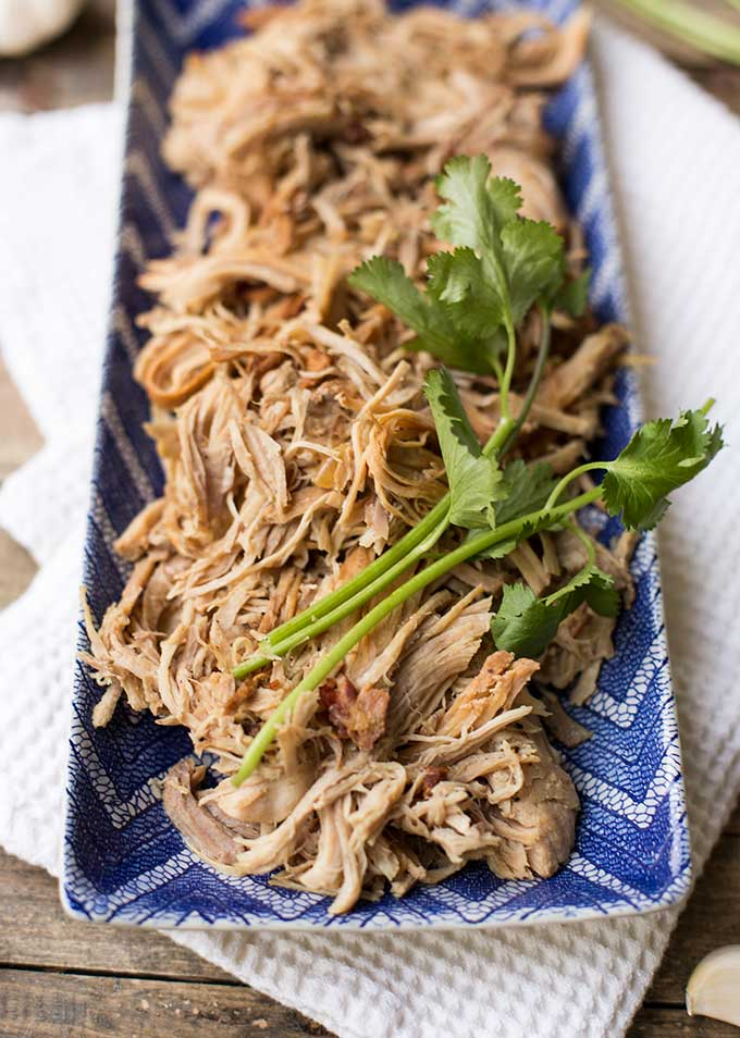 Instant Pot Kalua Pork: Just a few simple ingredients - bacon, garlic, onion, salt and pepper - turn a basic pork roast into a mouthwatering, tender, juicy dinner in 90 minutes, with almost no effort.