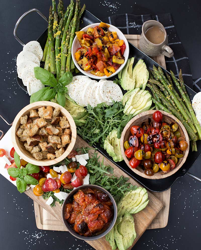 Asparagus Caprese Salad Board: Fresh mozzarella, tomatoes, basil, arugula and asparagus served on a platter with homemade croutons and balsamic dressing.