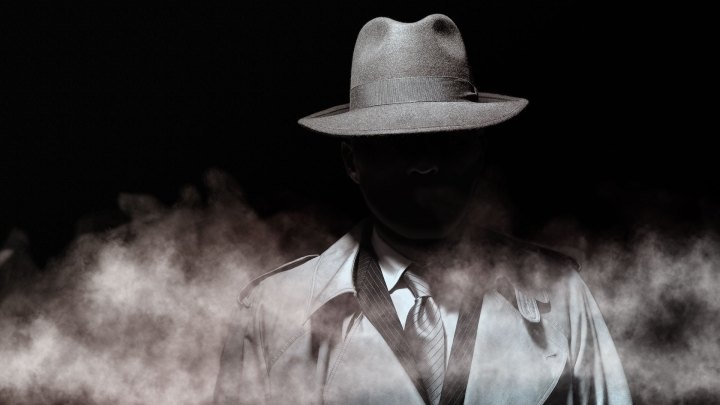 Dark constrasty image of man in fedora hat and trench coat walking in fog image.
