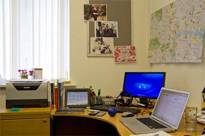 Phil's desk: MacBook, PC, iPad, iPod, smartphone, landline and stress ball.