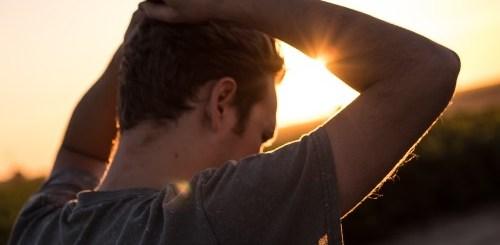 persona al sole preoccupata di spalle