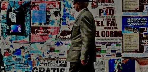Signore con cappello che passa davanti a parete con manifesti