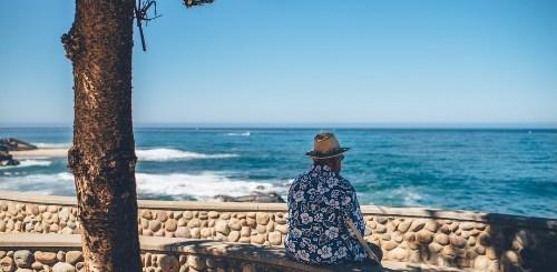 Signore anziano con camicia hawaiana che guarda il mare sotto ad un pino