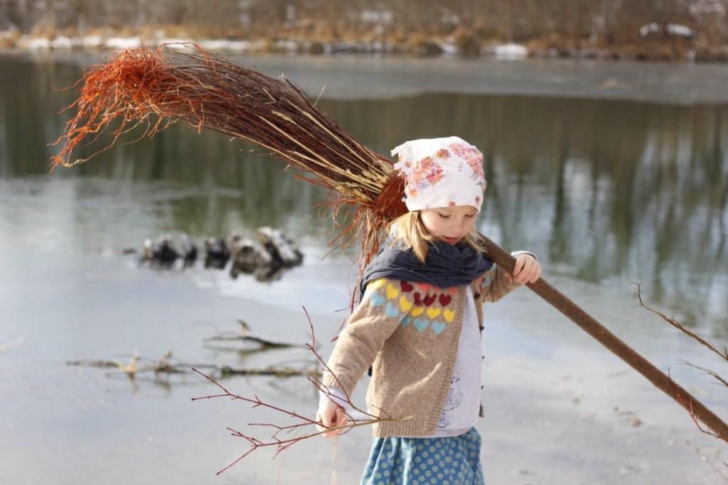 Mädchen am Wasser mit Hexenbesen