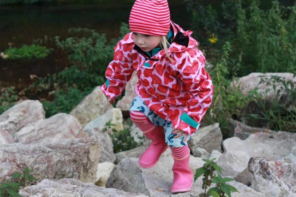 Mädchen auf großen Flußsteinen