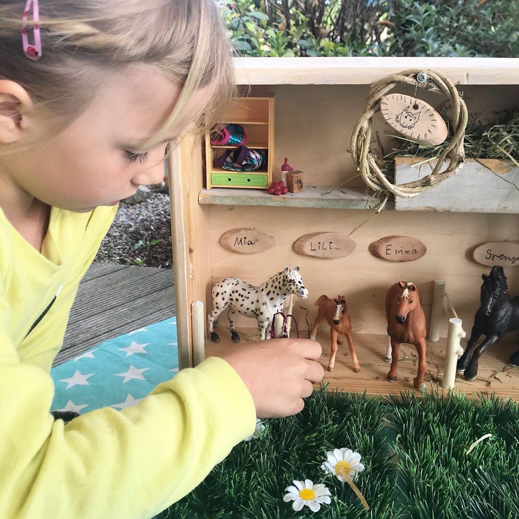 Mädchen spielt mit Schleich Pferdestall