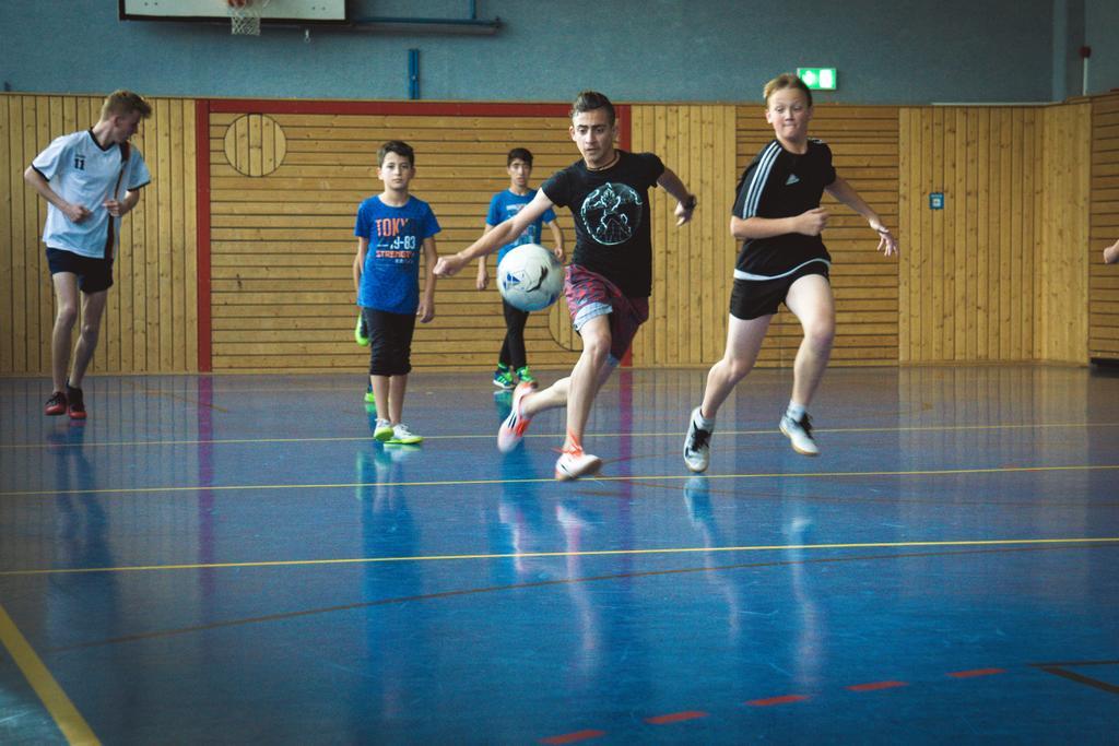 Kinder spielen Ball in einer Turnhalle.