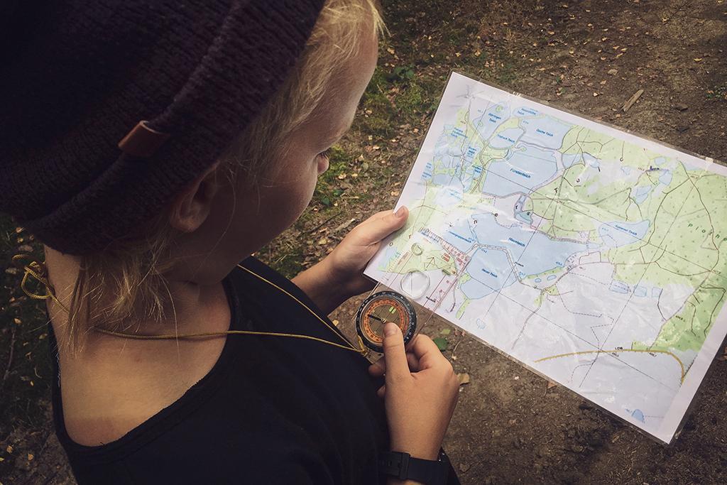 Mit einer Karte und Kompass kann man den richtigen Weg durch den Wald leichter finden.