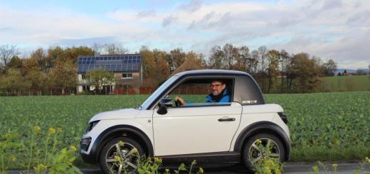 Gerd Bicker in seinem Tazzari, im Hintergrund die Photovoltaik-Anlage, die seinen lautlosen Flitzer antreibt