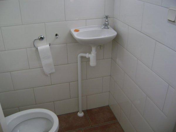 Afvoer wasbak toilet in muur verwerken