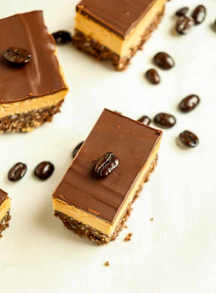 coffee Nanaimo bar with a coffee bean on top and coffee beans scattering around