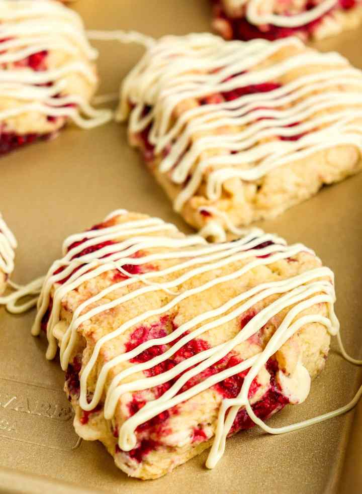 heart-shaped scone with raspberries and drizzled with white chocolate