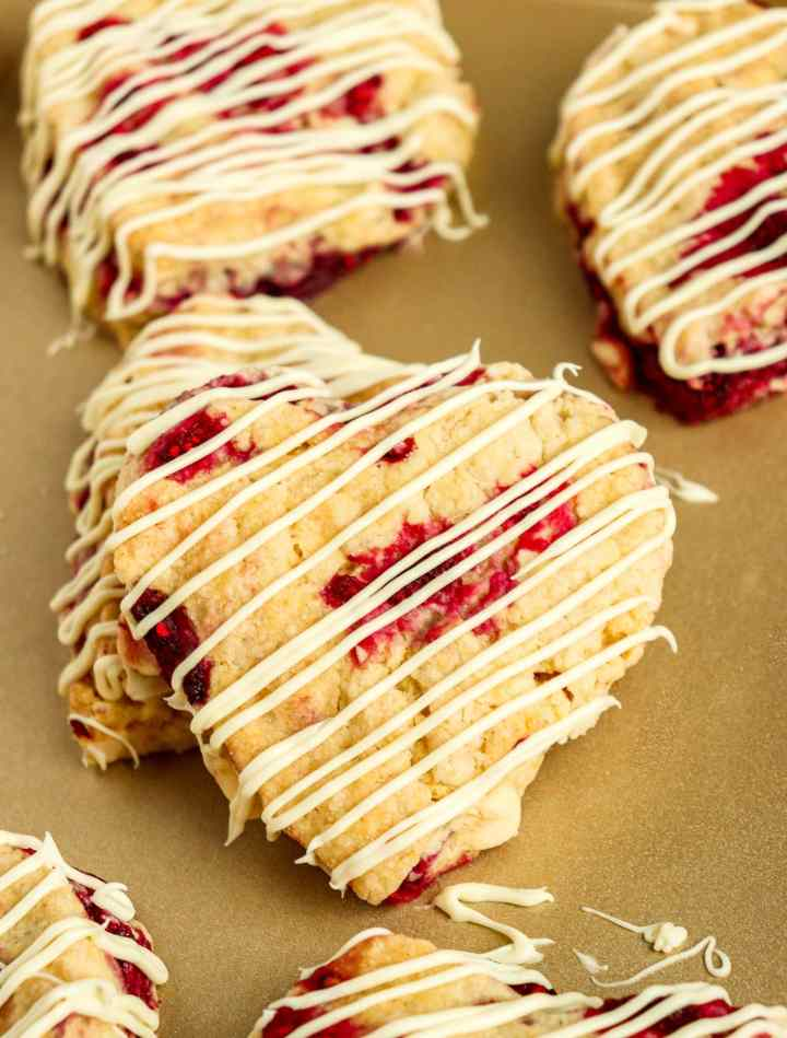 heart-shaped white chocolate raspberry scone with drizzled white chocolate on top