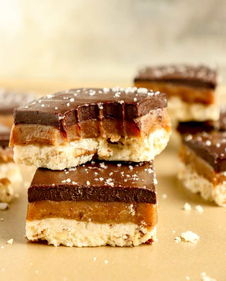 bars with a pecan shortbread crust, caramel filling, and chocolate topping, with flakey sea salt sprinkled on top
