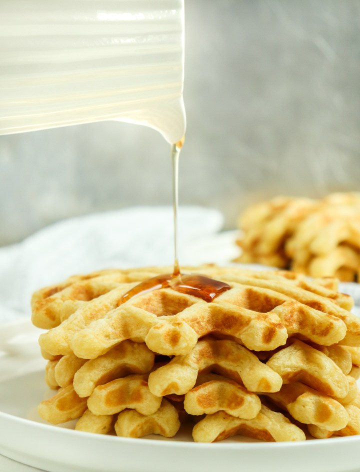 pouring syrup onto a stack of waffles