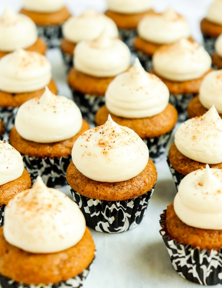 mini pumpkin cupcakes in floral cupcake wrappers topped with cream cheese frosting