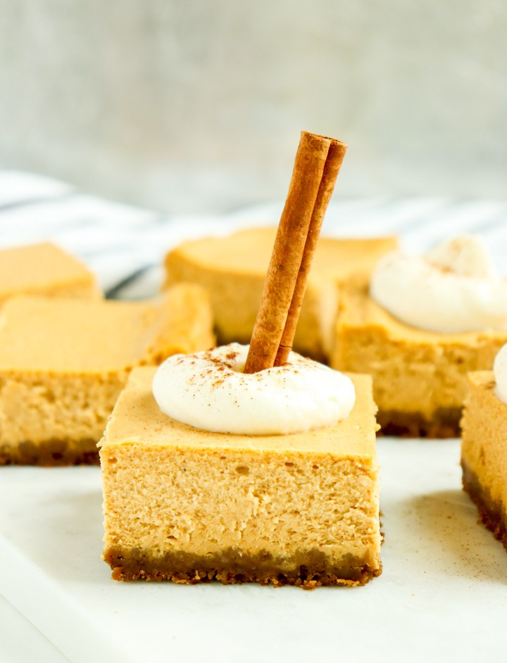 pumpkin cheesecake bar topped with whipped cream and a cinnamon stick
