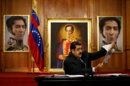 Venezuelan President Nicolas Maduro holds a newspaper as he speaks in front of images of South American hero Simon Bolivar in Caracas