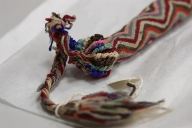 Brightly coloured sheath covered in woven yarn, with tassel