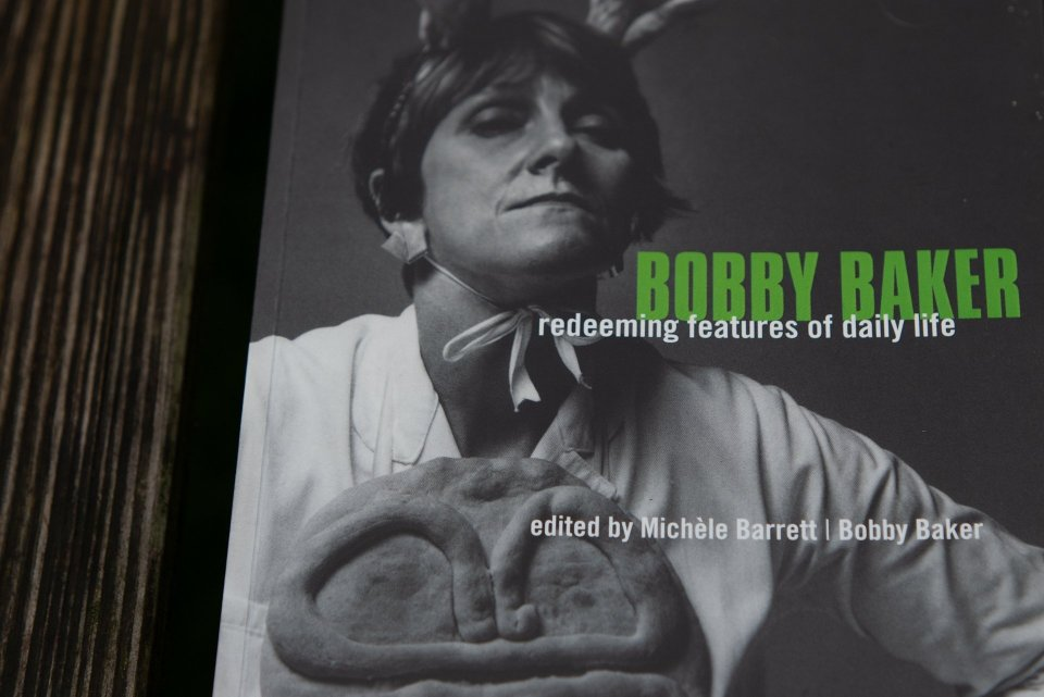 black and white book cover in which Bobby Baker is shown wearing white cookery overalls, a protective breast pizza and a pair of hand-baked antlers