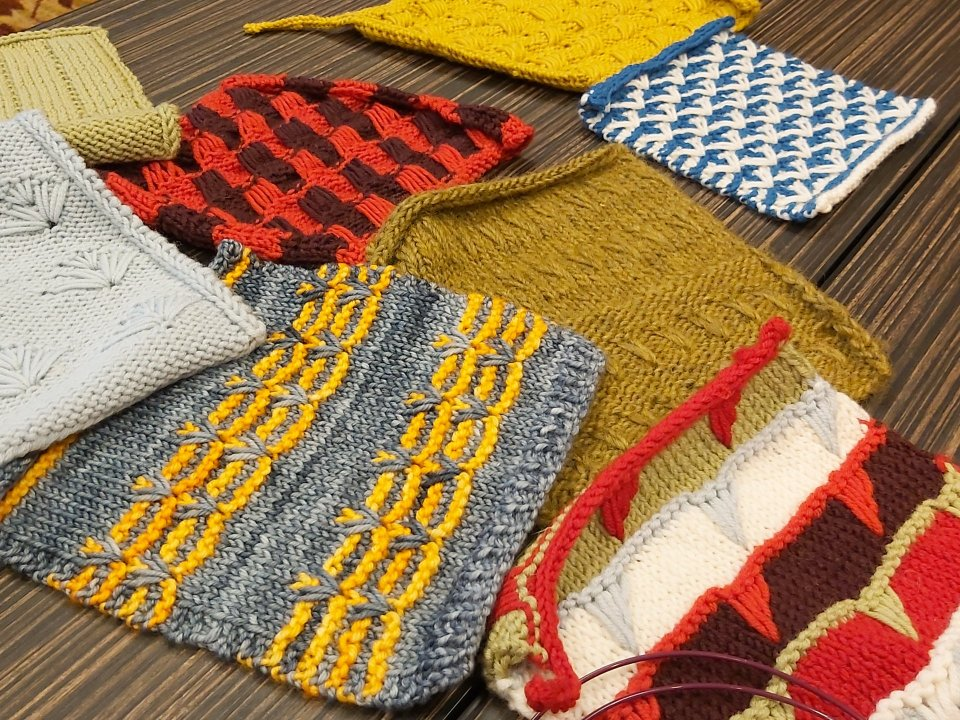 selection of hand-knitted swatches by Jeanette Sloan, featuring a variety of colours and variations on the dipped-stitch technique