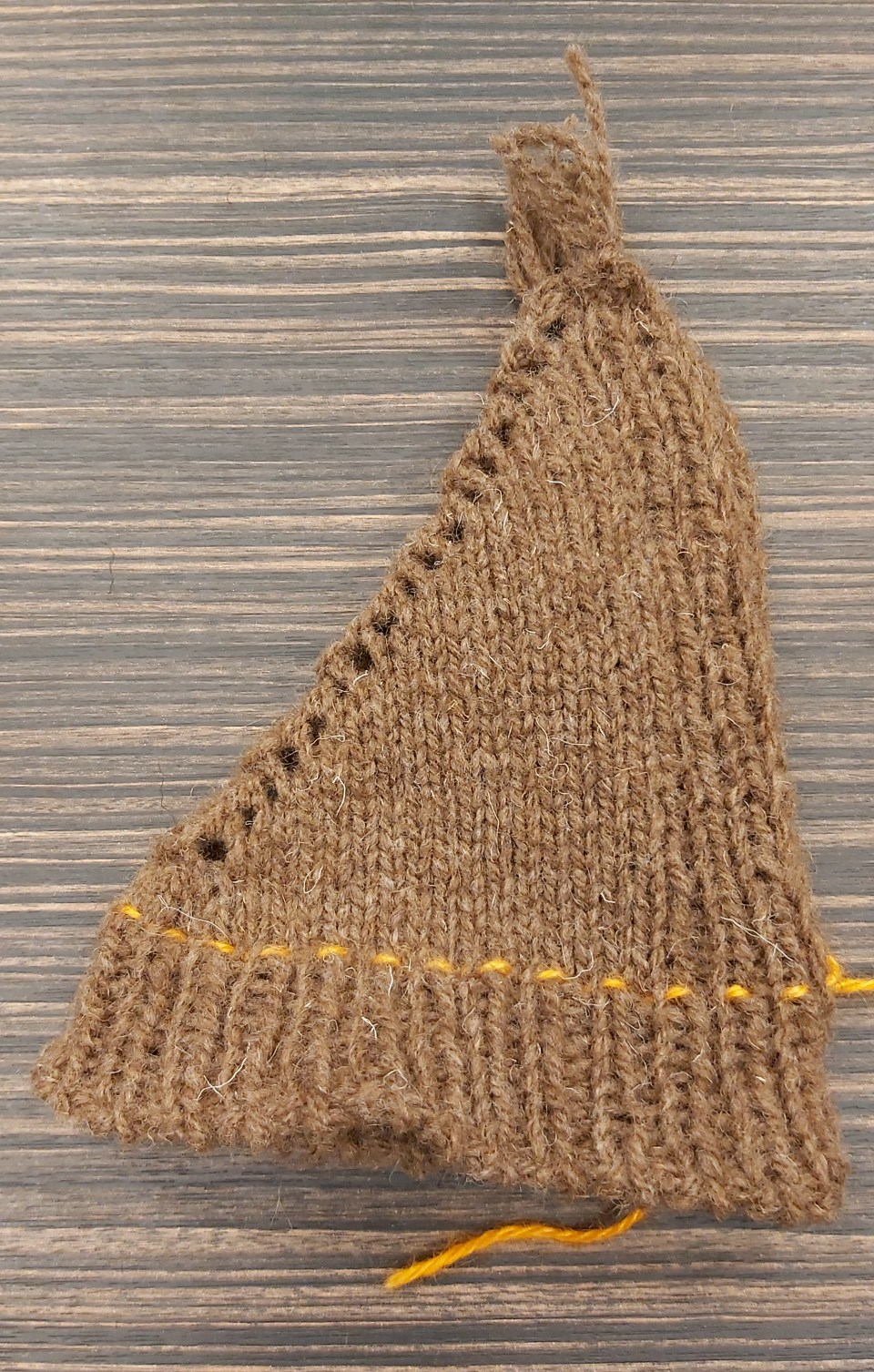 a brown cone of knitting with yarn-overs on one side and a neat selvedge on the other