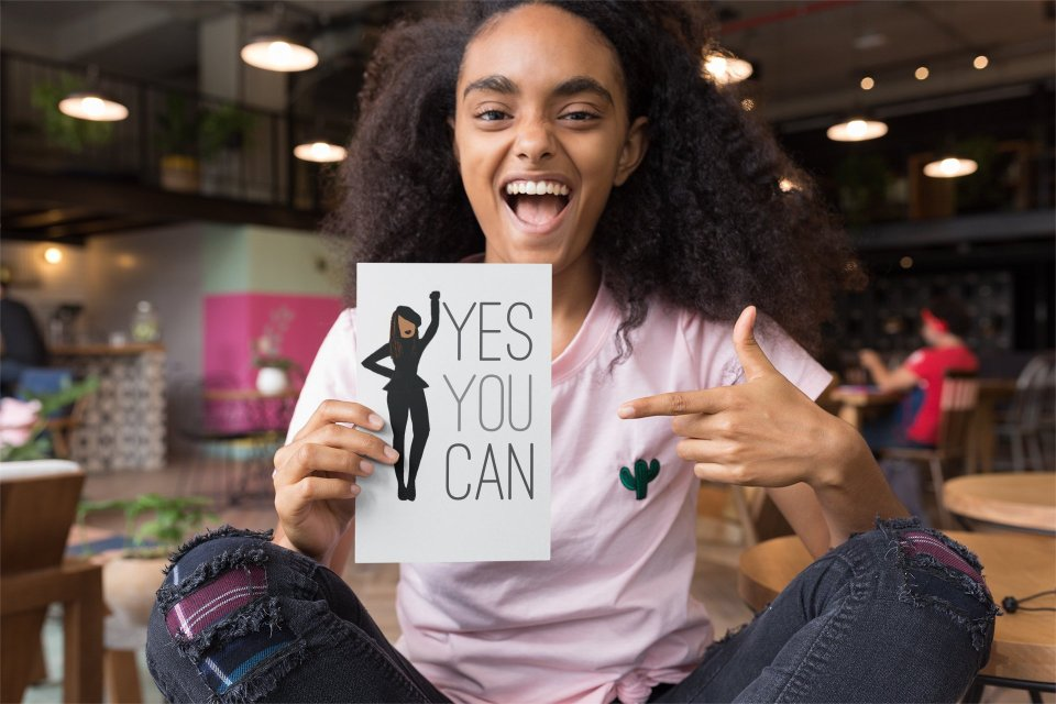 YES YOU CAN! A young black woman holds up, and points to, a glorious card in which a stylishly dressed black woman wearing smart black clothes and a jaunty beret points authoritatively to the words YES YOU CAN