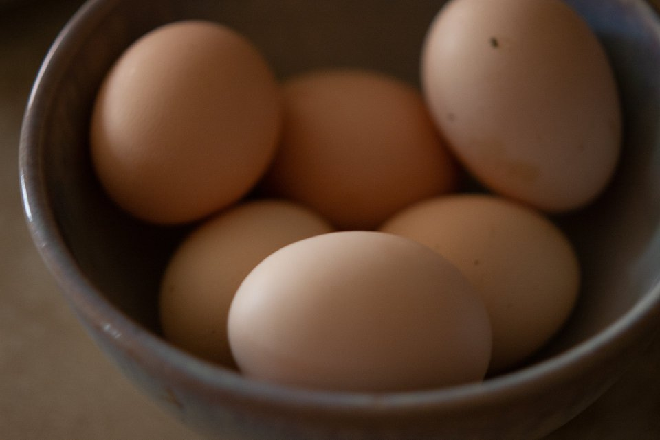 a bowl filled with lovely round chicken eggs