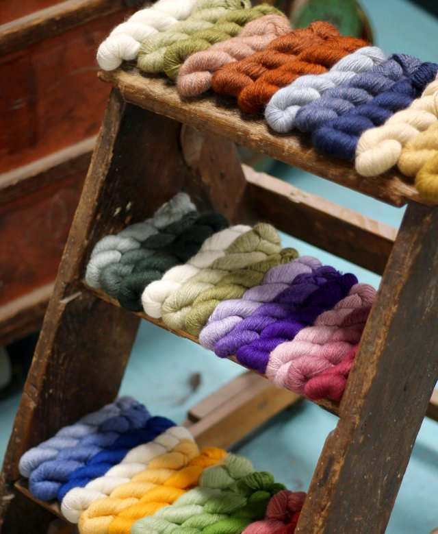 a worn and weathered wooden step-ladder bears three sets of glorious, glowing yarn skeins; they are purposefully arranged into sets of 12 skeins. The bottom is very bright and a bit rainbow-y; the middle one is jewel-tones with just a splash of hot, light greens; and the top one is a sort of neutral, murky palette of delight