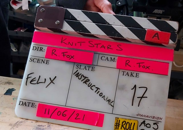 Joyful filming Clapperboard covered in turbo fluorescent pink tape - it says KNITSTARS / R. FOX / INSTRUCTIONAL / TAKE 17 / 11/06/21