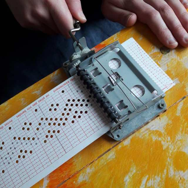 a hand winds the crank on a componium, causing a punch-card with a pattern of notes on it to travel through the mechanism.