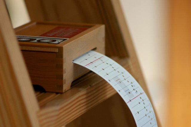 small programmable wooden music box set on a wooden ladder with a punch-card coming out of it.