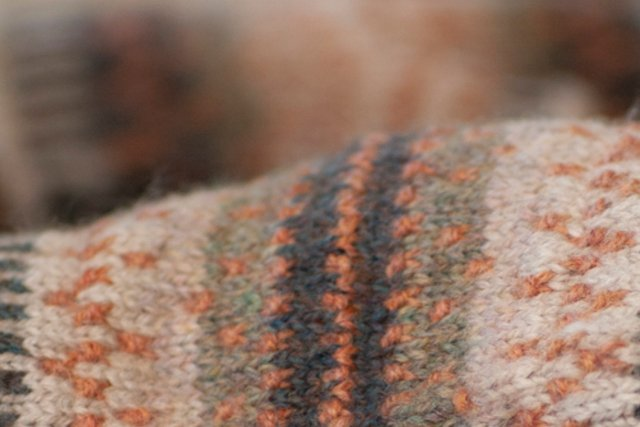 closeup of stranded colourwork fabric featuring little purl-bumps and a sort of mellowed palette of watery greens and a soft coral shade.