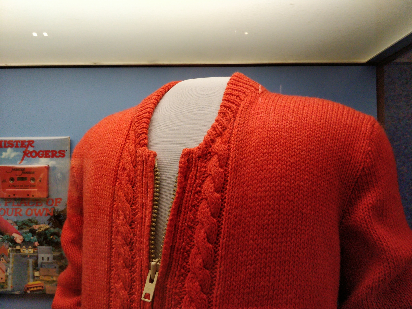 closer view of Mr. Rogers's sweater's collar and zipper pull