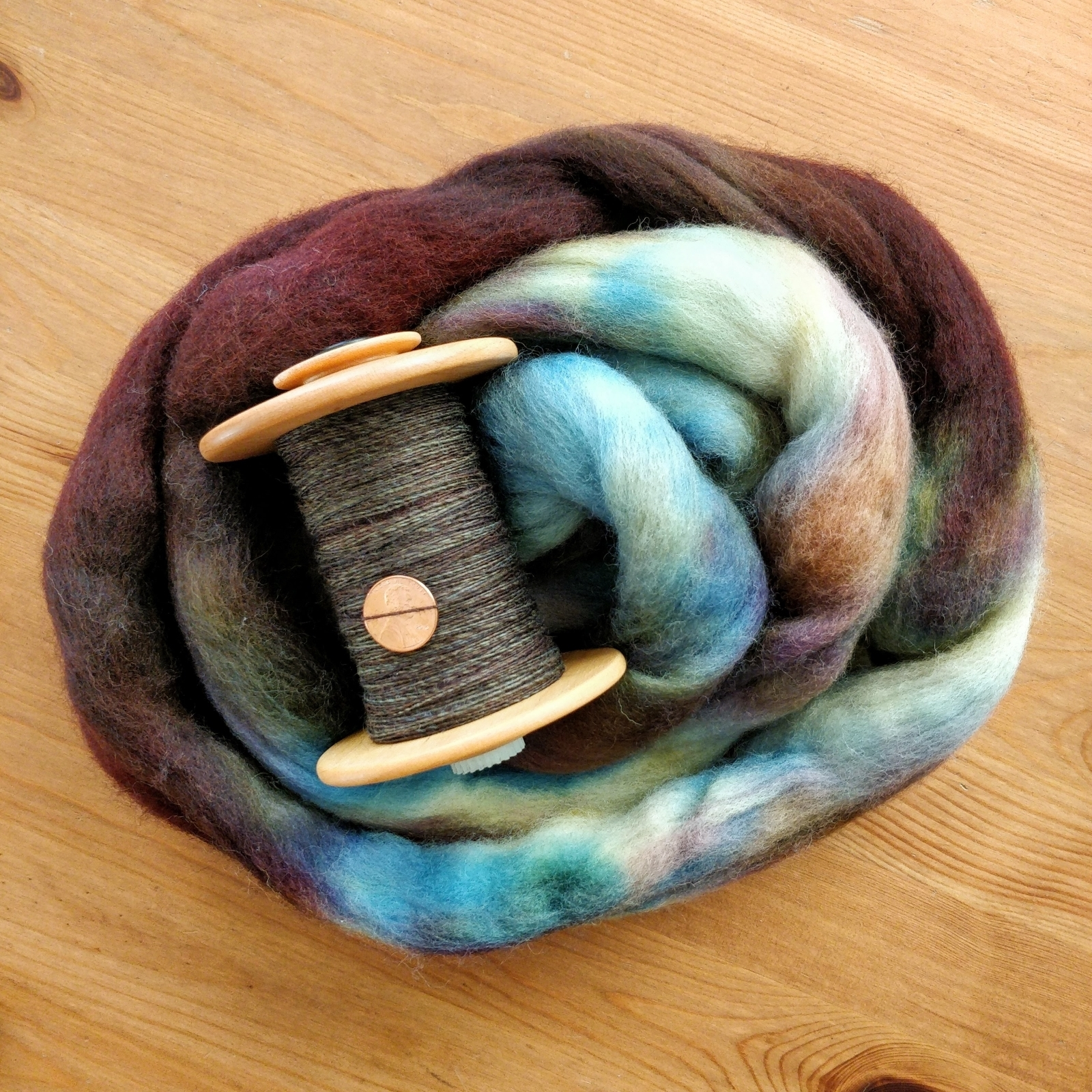 A bobbin of fine singles with a penny for scale rests on a nest of unspun wool.