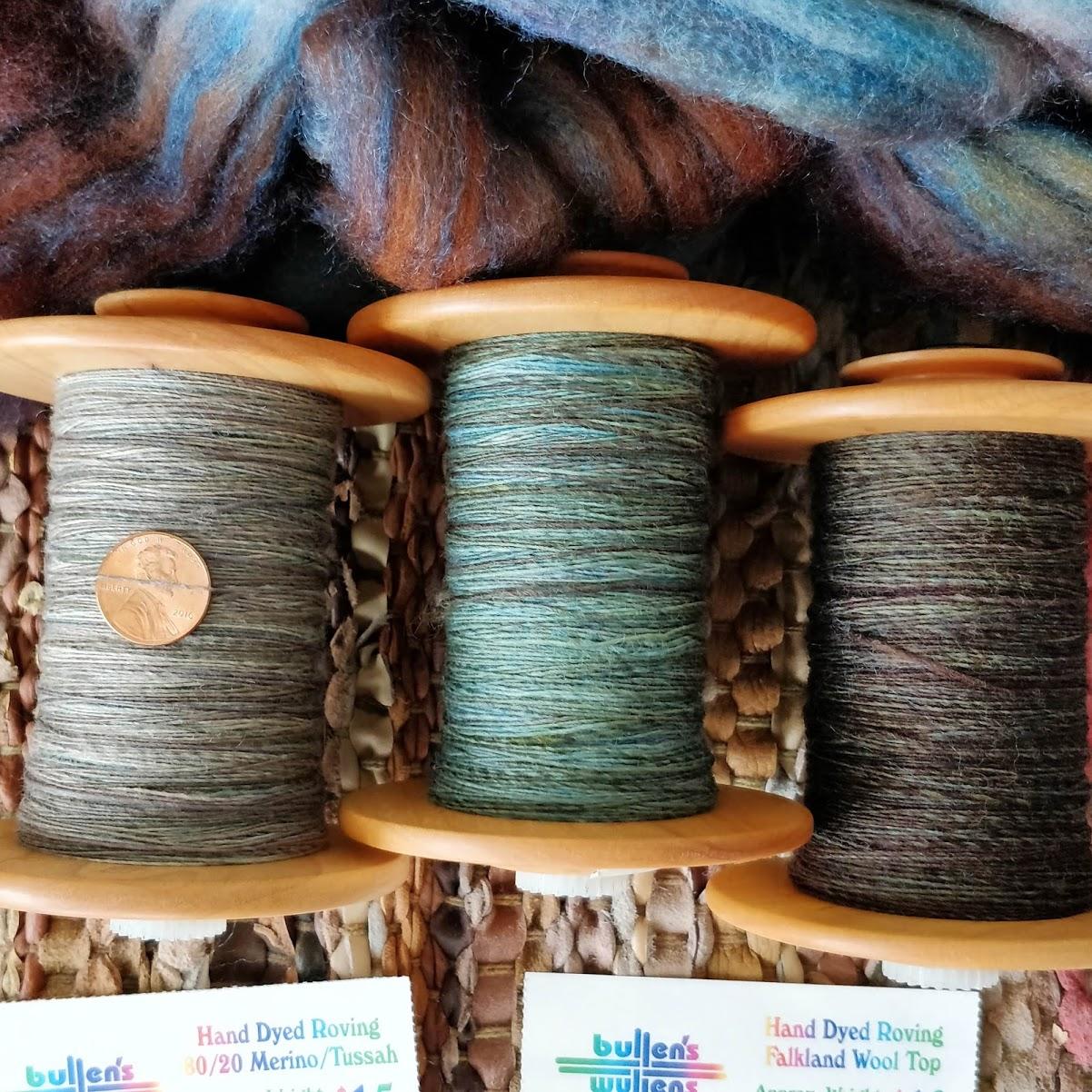 Three bobbins of fine singles with a penny for scale resting on a bit of blue and brown fibre.