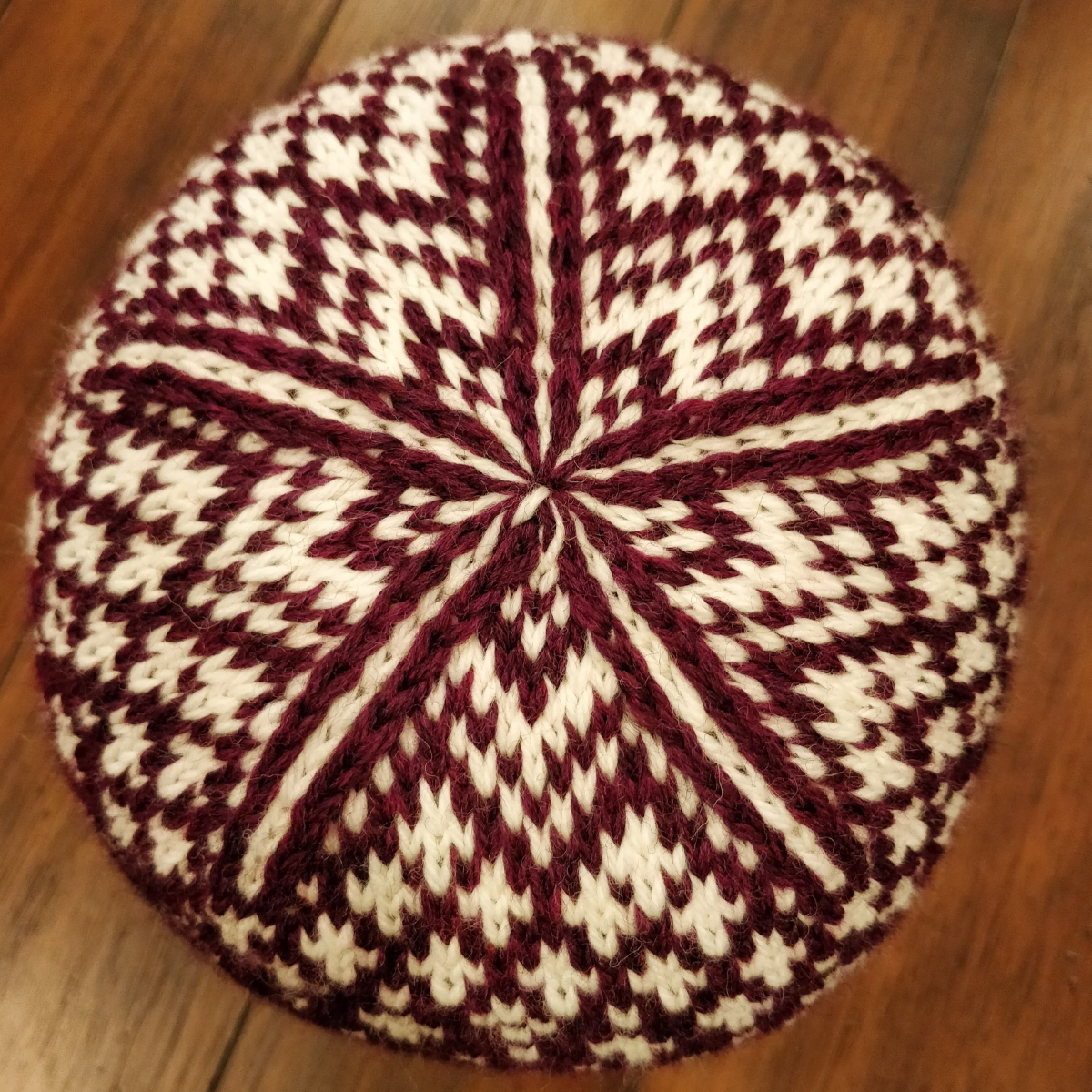 The top of a red and white hat. The stitches and colours form a star shape.